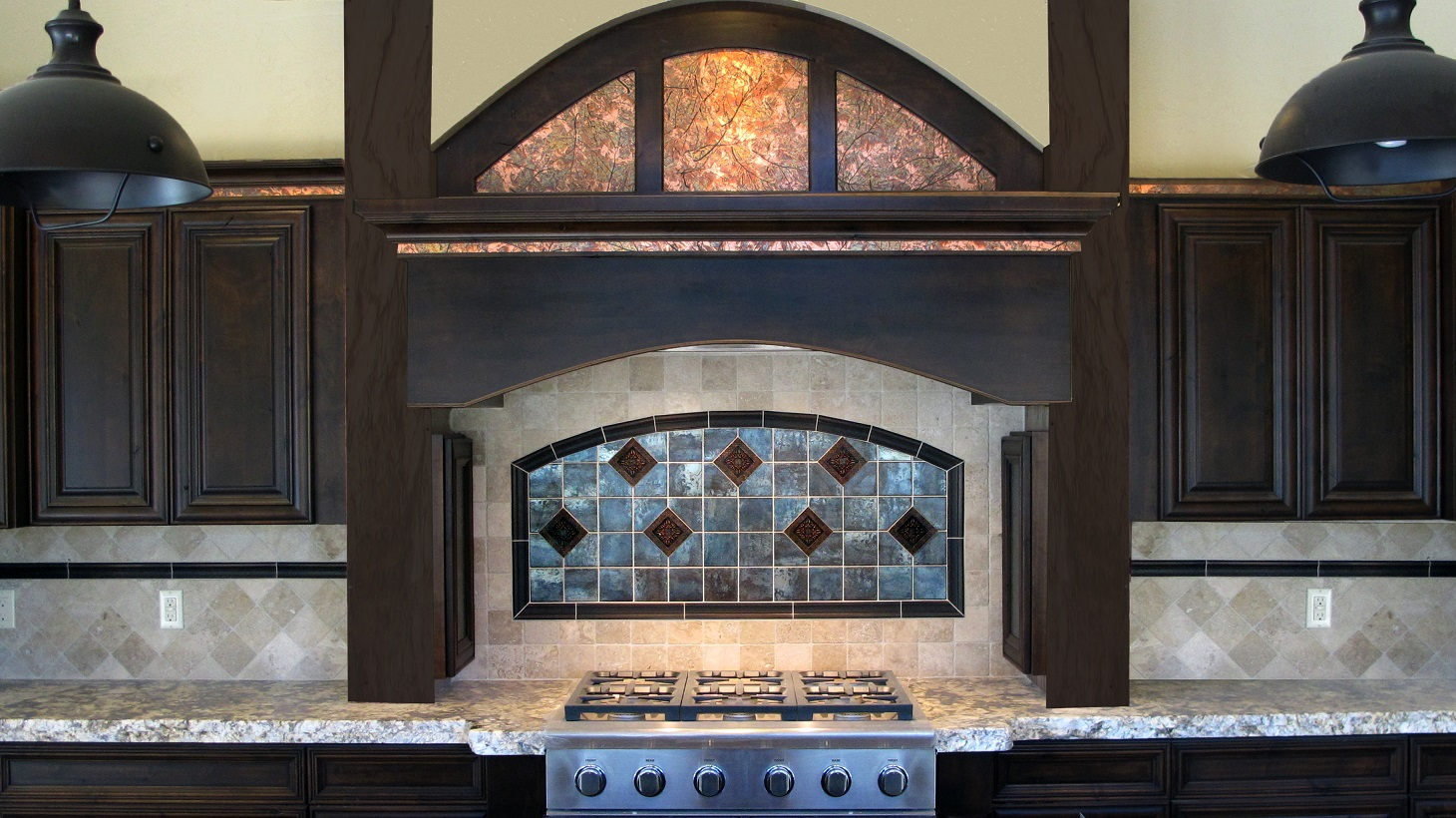 Kitchen rustic espresso cabinets custom arch gas range cook top granite countertops  travertine backsplash natural stone light beige metal metallic chair rail arch stove accent Emser Statements