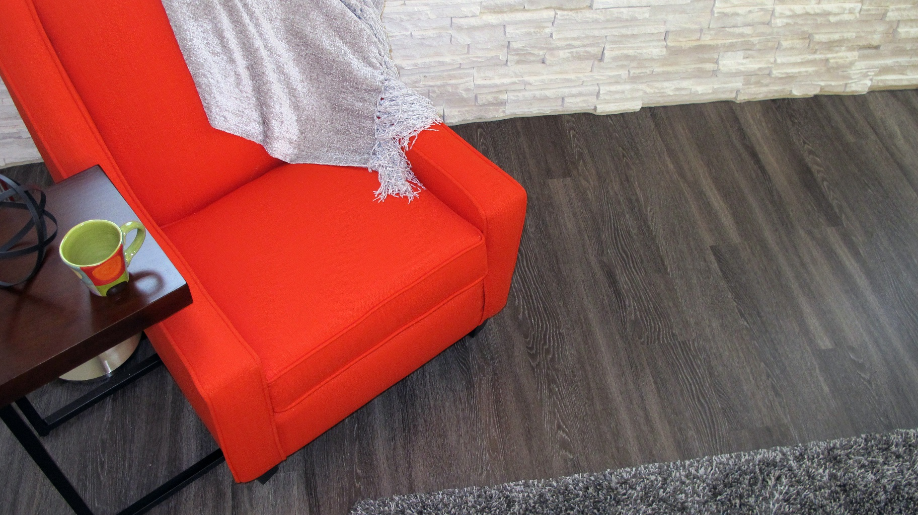 Luxury vinyl plank LVP shaw resilient Harwich Raven floating installation stone masonry white orange chair bright area rug
