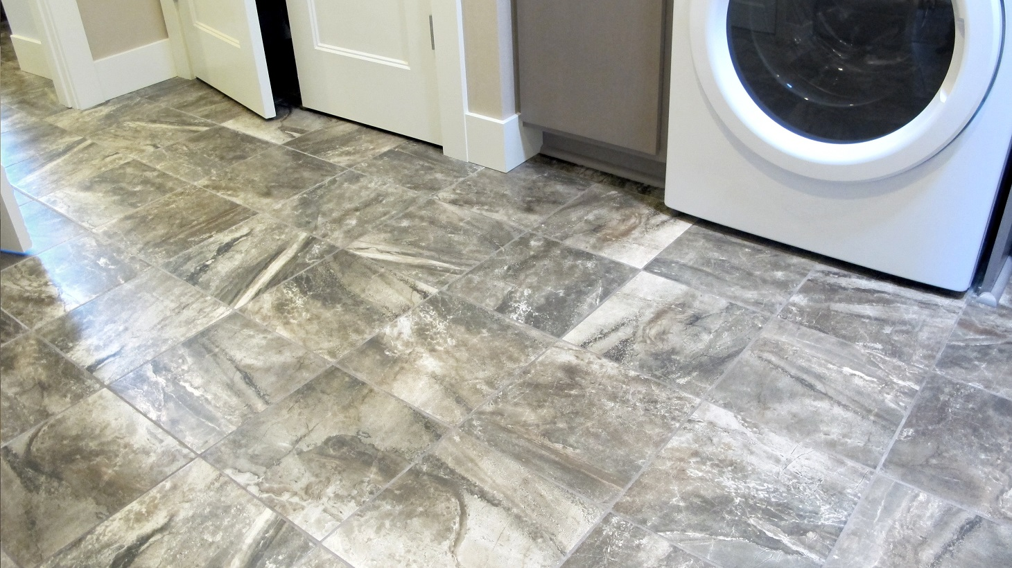 Laundry room white washer & dryer American Olean Danya Riverbed 12x12 brown pattern porcelain ceramic tile baseboard
