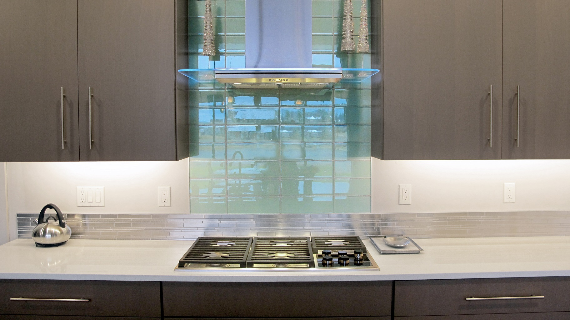 Aqua Blue Crystile 4x12 glass field tile Glazzio Soft Mint above a gas cook top arctic grey cabinets in the kitchen with Pental quartz perimeter.