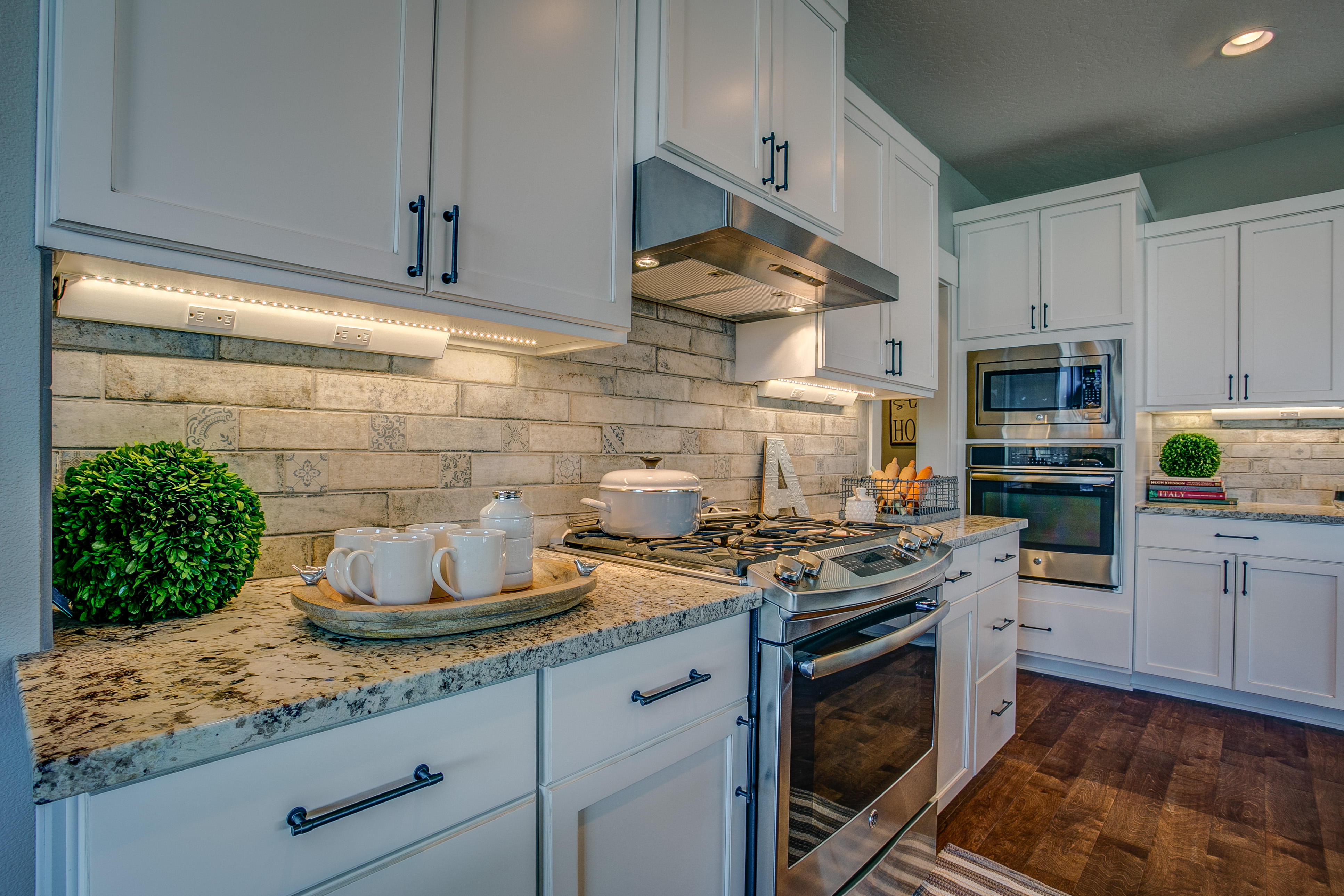 Kitchen backsplash with granite counters and white cabinets.