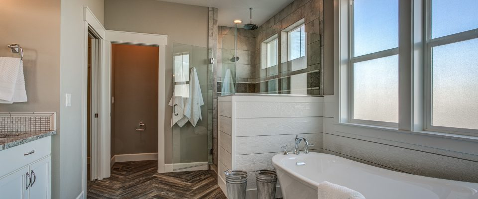 Master bathroom free-standing tub herringbone tile floor walk-in shower wainscot