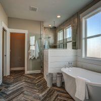Master bathroom free-standing tub herringbone tile floor walk-in shower wainscot